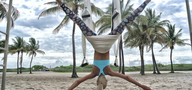 kobieta uprawiająca aerial joę na plaży